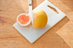 Grapefruit slice with knife Royalty Free Stock Images