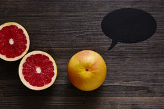Grapefruit with speechbubble and two halves.  Royalty Free Stock Photography
