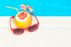 Grapefruit and sunglasses at the edge of swimming pool. Top down view of grapefruit with paper umbrella and drinking straw and red sunglasses at the edge of Royalty Free Stock Photography