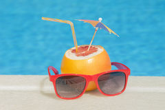 Grapefruit and sunglasses - poolside Stock Image