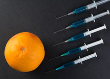 Grapefruit and syringe Stock Images