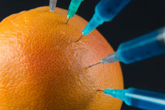 Grapefruit with syringes, close-up Royalty Free Stock Images