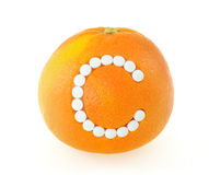 Grapefruit with vitamin c pills over white backgro stock photography