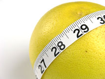Grapefruit Waistline. A measuring tape around a grapefruit. Great for the concept of diet, health, weight loss, waistline, fat Royalty Free Stock Photos