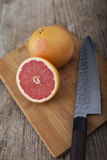 Grapefruit on wooden surface with knife Royalty Free Stock Images