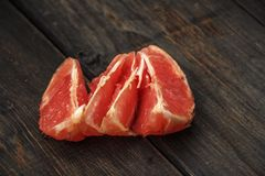 Grapefruit on a wooden table. Sliced ​​and whole grapefruit on a wooden board. Wooden background. Grapefruit on a wooden table. Sliced ​​and whole Royalty Free Stock Photography