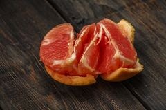 Grapefruit on a wooden table. Sliced ​​and whole grapefruit on a wooden board. Wooden background. Grapefruit on a wooden table. Sliced ​​and whole Royalty Free Stock Image