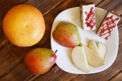 Grapefruitowy, zasycha i plasterki bonkreta w białym talerzu na drewnianym stole sosnowe deski Bufet w autentycznym naturalnym ho zdjęcie royalty free