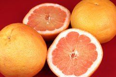 Grapefruits. Three Grapefruits ( one cut) on a red background Royalty Free Stock Photos