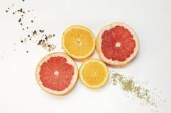 Grapefruits en sinaasappelen op witte achtergrond Vruchten met kruiden Rode, oranje, gele plakken van vruchten Peperkruiden op ac Royalty-vrije Stock Fotografie