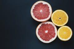 Grapefruits en sinaasappelen op zwarte achtergrond Plakvruchten behang Rode, gele, verse vruchten Royalty-vrije Stock Afbeelding