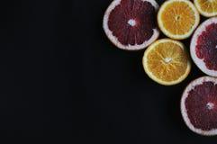 Grapefruits en sinaasappelen op zwarte achtergrond Plakvruchten in de hoek Rood, yellpw, sappige vruchten Stock Foto's