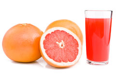 Grapefruits and glass of juice. Grapefruits and glass of juice are isolated on the white. Cut of grapefruit Stock Photos