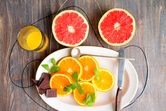 Grapefruits, grapefruit halves and slices, chocolate, orange and orange slices and segments, mint leaves Royalty Free Stock Photos