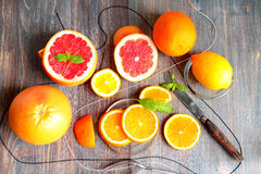 Grapefruits, grapefruit halves and slices, lemon, orange and orange slices and segments, mint leaves and knife Stock Photography