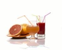 Grapefruits i grapefruitowy sok na białym gackground zdjęcie royalty free