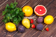 Grapefruits, pears, lemons, figs, strawberry, pomelo and mint; still life with fruits Royalty Free Stock Images