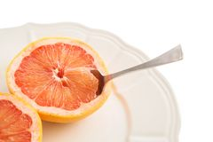 Grapefruits on plate with spoon. Grapefruits on old white plate with spoon on plate on white background Stock Photography