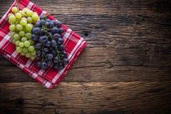 grapefruits Wiązka stubarwni winogrona na nieociosanym drewnianym stole fotografia royalty free