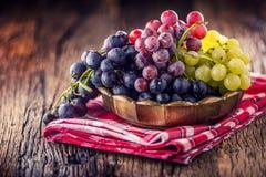 grapefruits Wiązka stubarwni winogrona w retro pucharze na starej dębowej zakładce zdjęcia royalty free