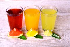 Grapefrukt apelsiner, limefrukt - citrusa fruktsafter i exponeringsglas royaltyfri fotografi