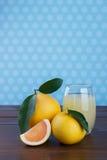 Grapefrukt och fruktsaft på trätabellen Royaltyfri Bild