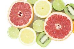 Grapefrukten limefrukt, citronen, kiwi är på en vit bakgrund royaltyfri fotografi