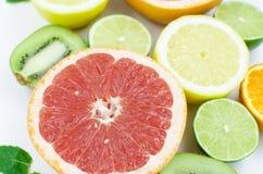Grapefrukten limefrukt, citronen, kiwi är på en vit bakgrund royaltyfri foto