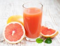 Grapefruktfruktsaft och mogna grapefrukter Arkivbild