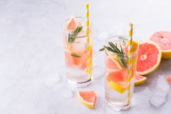 Grapefruktlemonad Två exponeringsglas av uppfriskande drink, vatten med grapefrukten, rosmarinfilialer och is royaltyfria bilder