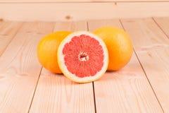 Grapefruktsegment på en trätabell Fotografering för Bildbyråer
