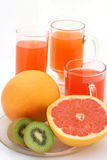 Grapegruit and kiwi with juice. Cutted grapefruit and kiwi with three glass of grapefruit juice on background Stock Photo