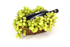 Grapes. With a bottle of wine in a wicker basket Royalty Free Stock Photos