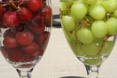 Grapes. Two glasses filled with red and green grapes Royalty Free Stock Images