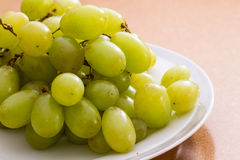 Grapes. Bunch of fresh green grapes on a white plate Stock Photos