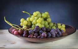 Grapes. Red and green grapes in a glass bowl on a wooden table Stock Photos