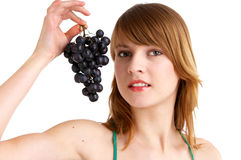 Grapes. Young woman holds grapes in her fingers Stock Images