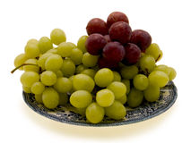 Grapes. Juicy, sweet green and purple grapes on a porcelain plate Royalty Free Stock Image