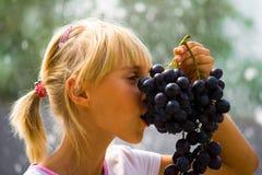 Grapes. Summer vacation. A young girl eating grapes royalty free stock photo