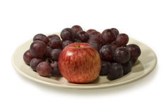 Grapes and apple. Red apple and grapes on a plate. On a white background Stock Photo