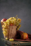 Grapes and apples in a basket Stock Photography