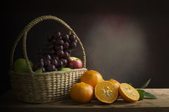 Grapes, apples and oranges  in a in wicker basket on a wooden ta Royalty Free Stock Photo