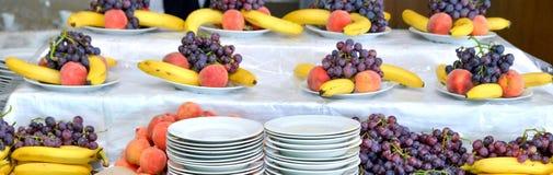 Grapes, bananas, oranges, on a table Stock Photos