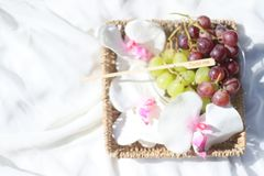 Grapes in a basket with flowers on grass royalty free stock photos