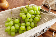 Grapes in a basket. On an old wooden table Stock Images