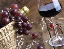 Close on wineglass for tasting. Grapes on a basket to serve wine with a bottle and a part of a wineglass Stock Image