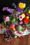 Grapes and big flower arrangement on wood table. Modern interpretation of classical still life style stock images
