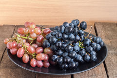 Grapes in black plate Royalty Free Stock Photography