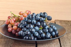 Grapes in black plate Royalty Free Stock Images