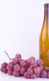 Grapes with bottle on white Stock Image